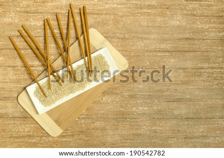 Chopsticks, a bamboo cutting board and uncooked brown rice on a white rectangular plate