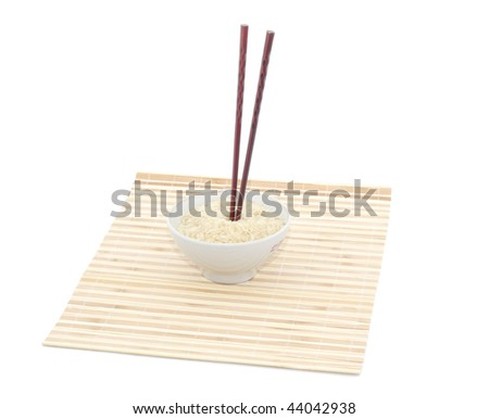 Chopsticks and bowl on bamboo mat. Isolated object. - stock photo