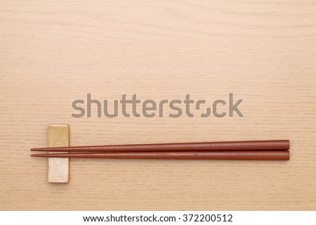 Chopsticks and chopsticks rest on table background  - stock photo