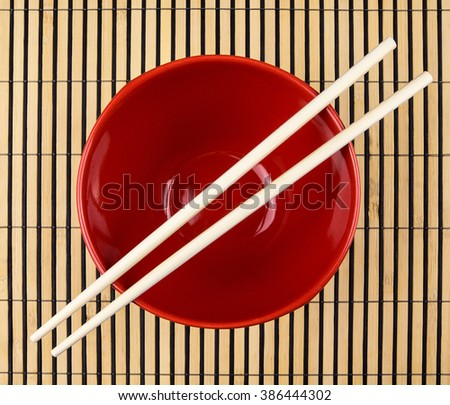 Chopsticks and dipping saucer arranged on sushi bamboo mat - stock photo