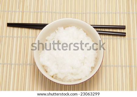 chopsticks and tureen with rice on bamboo tray