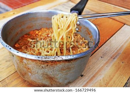 Chopsticks holding asian noodles in pot - stock photo