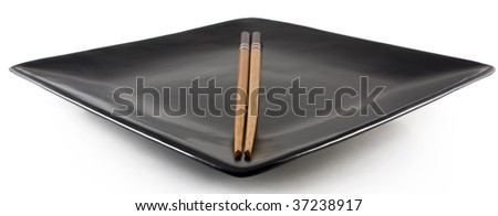 Chopsticks on a empty black chinese plate - stock photo
