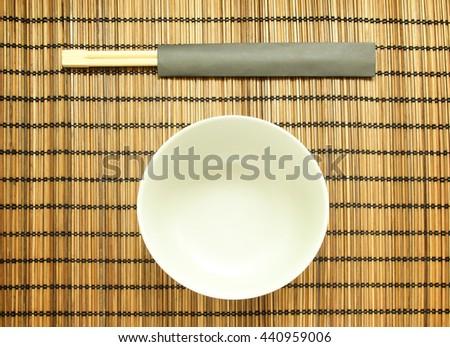 Chopsticks on bamboo matting background - stock photo