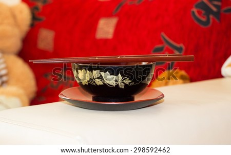 Chopsticks on red and black Japanese bowl in the interior - stock photo