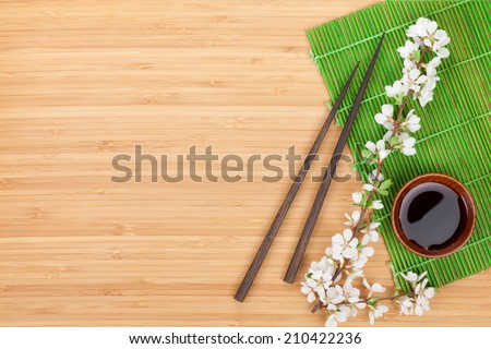 Chopsticks, sakura branch, soy sauce and bamboo mat on wooden table with copy space - stock photo