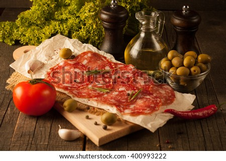 Chorizo sausage and salami, thin cut. spanish salami on the wood background with spices, paprika, pepper. Spicy food. Garlic, tomato, salad background. - stock photo