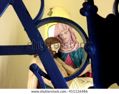 Christ and Mary, figure behind a grid - stock photo