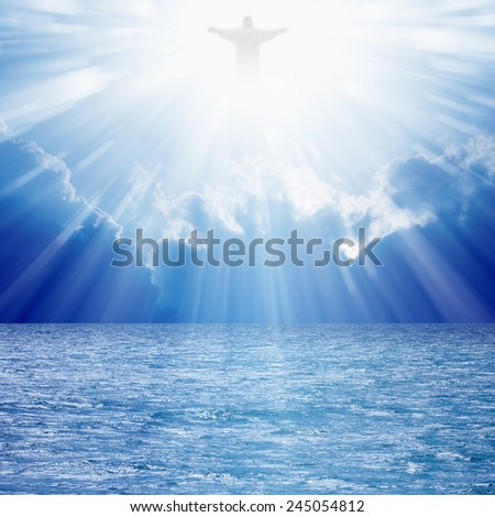 Christ silhouette in blues skies over sea, bright light from heaven - stock photo