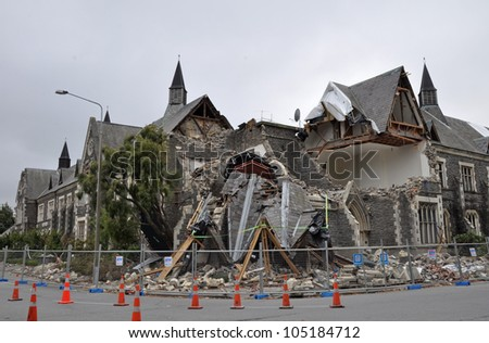 CHRISTCHURCH, NEW ZEALAND - MARCH 12: The old Normal School Building on the corner of Montreal and Kilmore streets collapses after a huge earthquake on March 12,  2011 in Christchurch. - stock photo