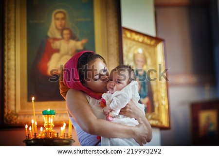 Christening ceremony. Family celebrating baptism in Orthodox Church. A young beautiful mother in the pink headscarf holding  her new-born baby in her arms and kissing the girl. - stock photo