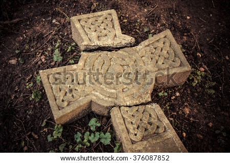 Christian beliefs - Time and traditions - Broken cross. Ancient broken Celtic cross laying on the ground at an English graveyard. - stock photo