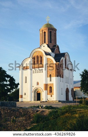 Christian church historical reconstruction Ancient Rus' with white plaster and open plinth on a sunny day with clear blue sky - stock photo