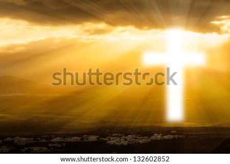 Christian cross glows against the rising sun - stock photo
