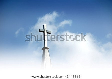 Christian cross in clouds and against blue sky		 - stock photo