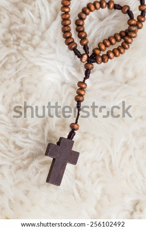 Christian cross necklace on sheep wool, Jesus religion concept as good friday or easter festival - stock photo