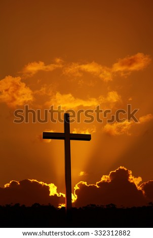 Christian cross over dramatic sunset vertical image
