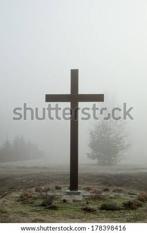 christian cross silhoutte in foggy morning - stock photo