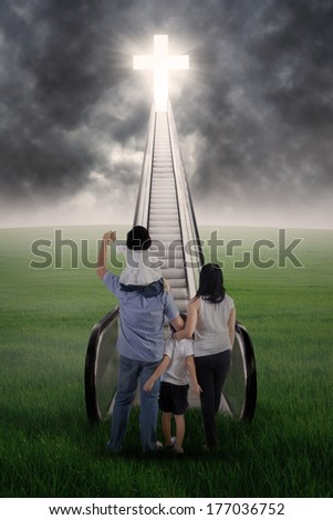 Christian family are standing on the stairs and looking at the bright Cross - stock photo
