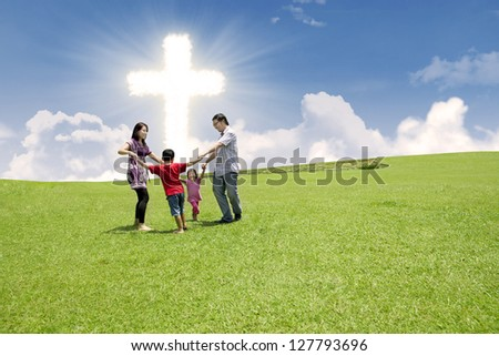 Christian family enjoying their Easter holiday in the park under bright Cross sign - stock photo