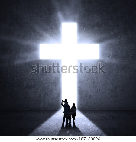 Christian family walking towards a Cross of Jesus - stock photo