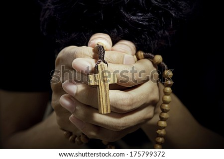 Christian man praying with rosary in hands - stock photo