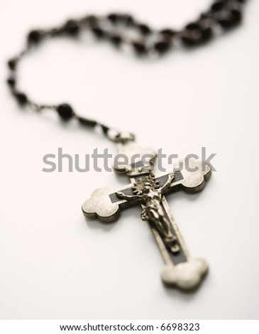 Christian rosary beads with crucifix on white background. - stock photo