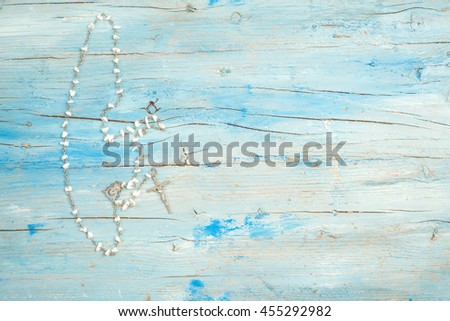 Christian rosary on blue rustic wood with space for writing text - stock photo