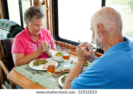Christian senior couple saying grace over a meal in their motor home. - stock photo