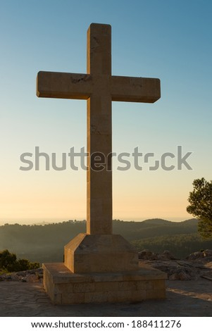 Christian stone cross under the warm light of sunrise