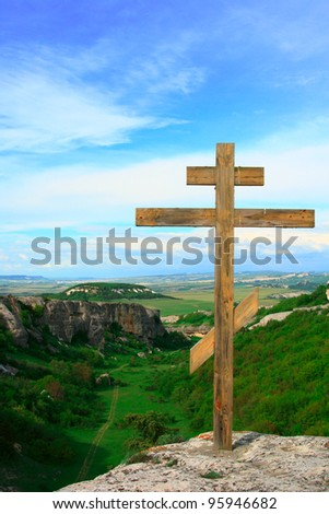 Christian wooden cross at top of mountain with a kind on a green valley and the dark blue sky with clouds