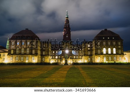 Christiansborg Palace in central Copenhagen at night. Cristiansborg castle in Denmark. Night lights and shadows wide angle view. - stock photo