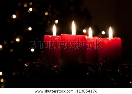 Christmas advent wreath with red burning candles. Lights on x-mas tree in background - stock photo