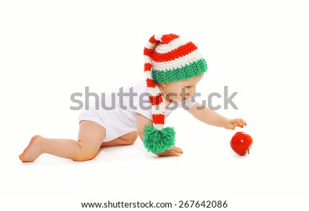 Christmas and childhood concept - baby in bright knitted gnome hat with red apple - stock photo