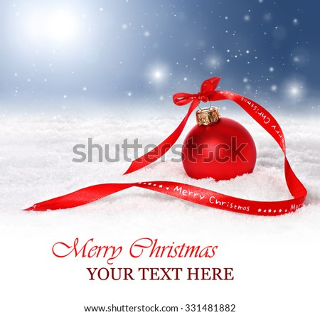 Christmas and holiday background with red ornament and merry christmas ribbon in snow. Snowflakes are falling from a blue sky.