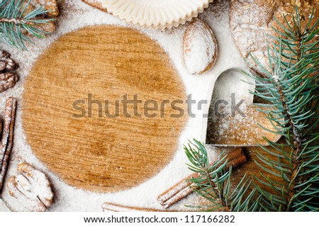 Christmas and holiday baking, cookies, flour, spruce branches and round space for text on a wooden board, ready template - stock photo