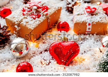 Christmas and New year background with presents, ribbons, balls and different decorations on snow. Bright decoration in shape of heart, symbol of love.