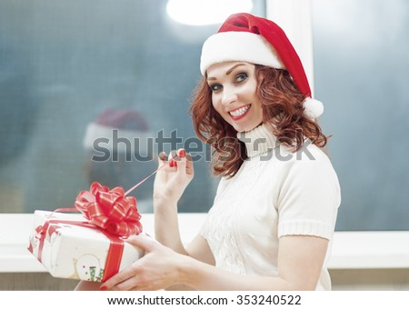Christmas and New Year Celebration and Holiday Concept. Caucasian Red-Haired Santa Girl Unwrapping Gift Box with Positive Facial Expression. Indoors Shot. Horizontal Composition