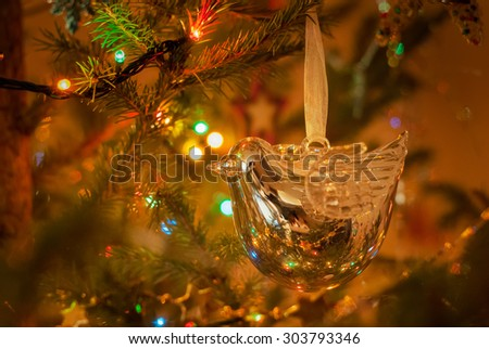 Christmas and New Year decoration. Beautiful silver bird bauble and lanterns are hanging on the Christmas tree. Holiday glowing background. - stock photo