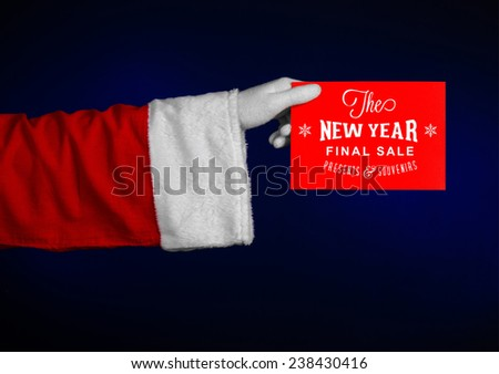 Christmas and New Year discounts topic: Hand of Santa Claus holding a red card with a Christmas discount on an isolated dark blue background
