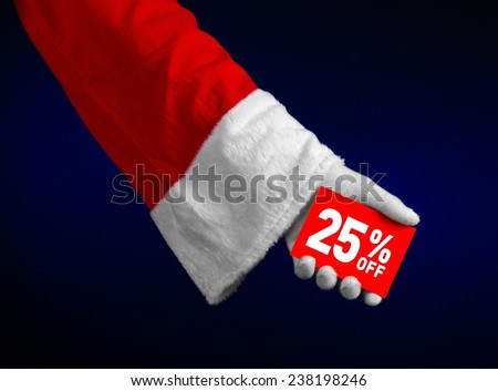 Christmas and New Year discounts topic: Hand of Santa Claus holding a red card with 25 % discount on an isolated dark blue background - stock photo