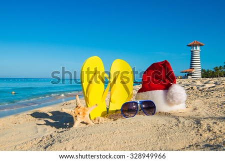 Christmas and New Year holidays at the sea. Santa hat, sandals, sunglasses on sandy beach - stock photo