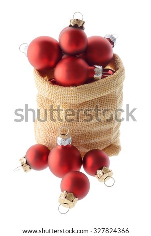 Christmas and New Year: lot of red Christmas tree balls, placed in and around Santa Claus bag, isolated on white background - stock photo