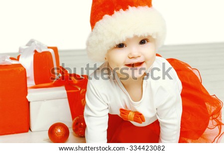 Christmas and people concept - cute smiling child in santa red hat with boxes gifts closeup - stock photo