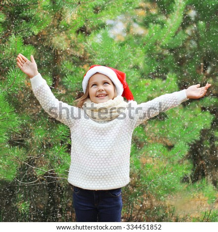 Christmas and people concept - little girl child in santa red hat enjoying snow - stock photo