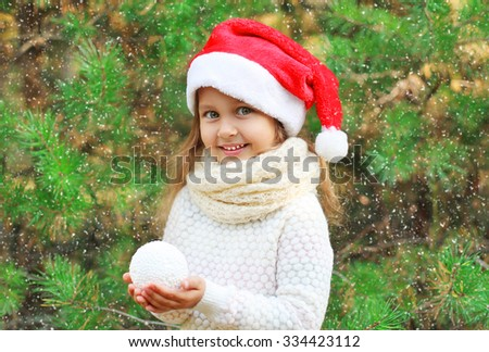 Christmas and people concept - little smiling girl child in santa red hat with snowball - stock photo