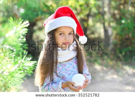 Christmas and people concept - portrait little child in santa red hat with snowball