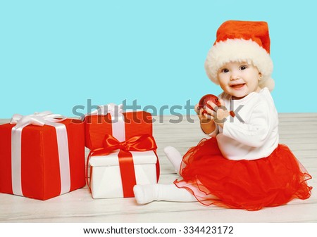 Christmas and people concept - smiling child in santa red hat with boxes gifts sitting on floor - stock photo