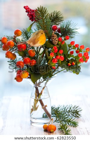 Christmas arrangement of ornamental apples(malus),fir branch and holly in vase - stock photo