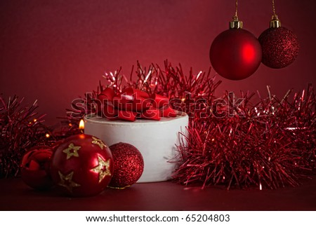 Christmas arrangement with gift, baubles and candle in red colors
